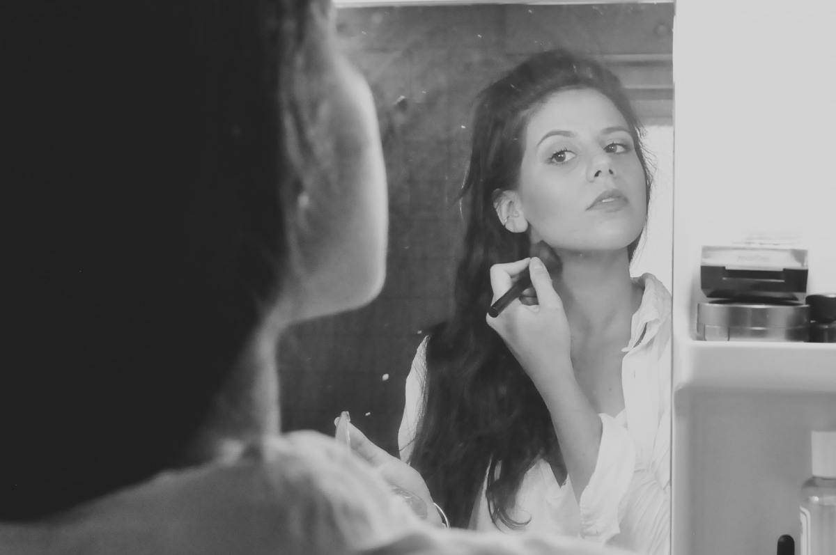 black and white photo woman looking in mirror putting on makeup