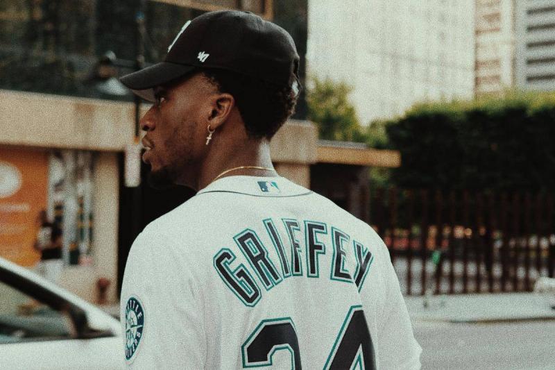 man walking wearing baseball jersey