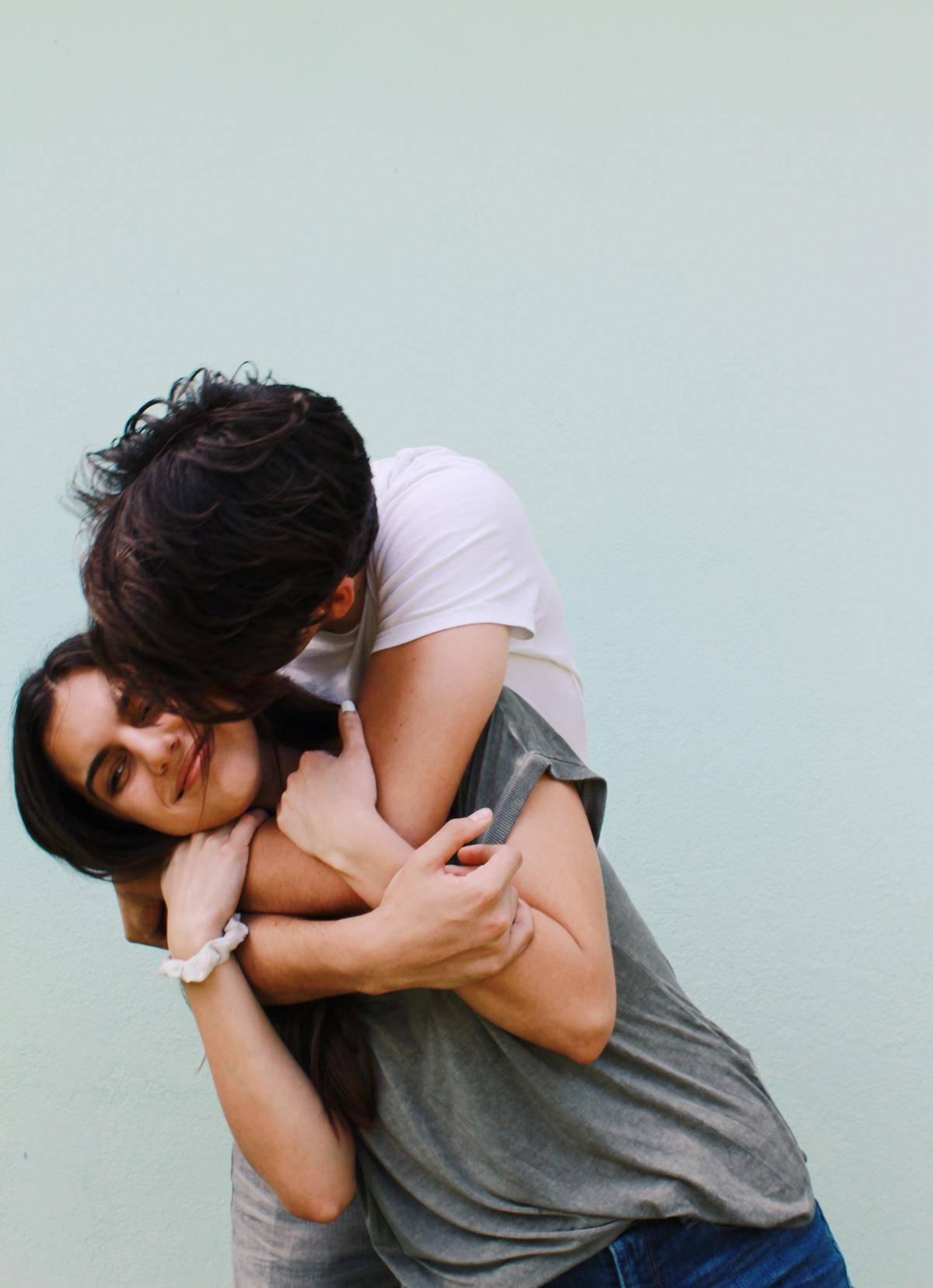 a guy giving a girl a hug and kiss