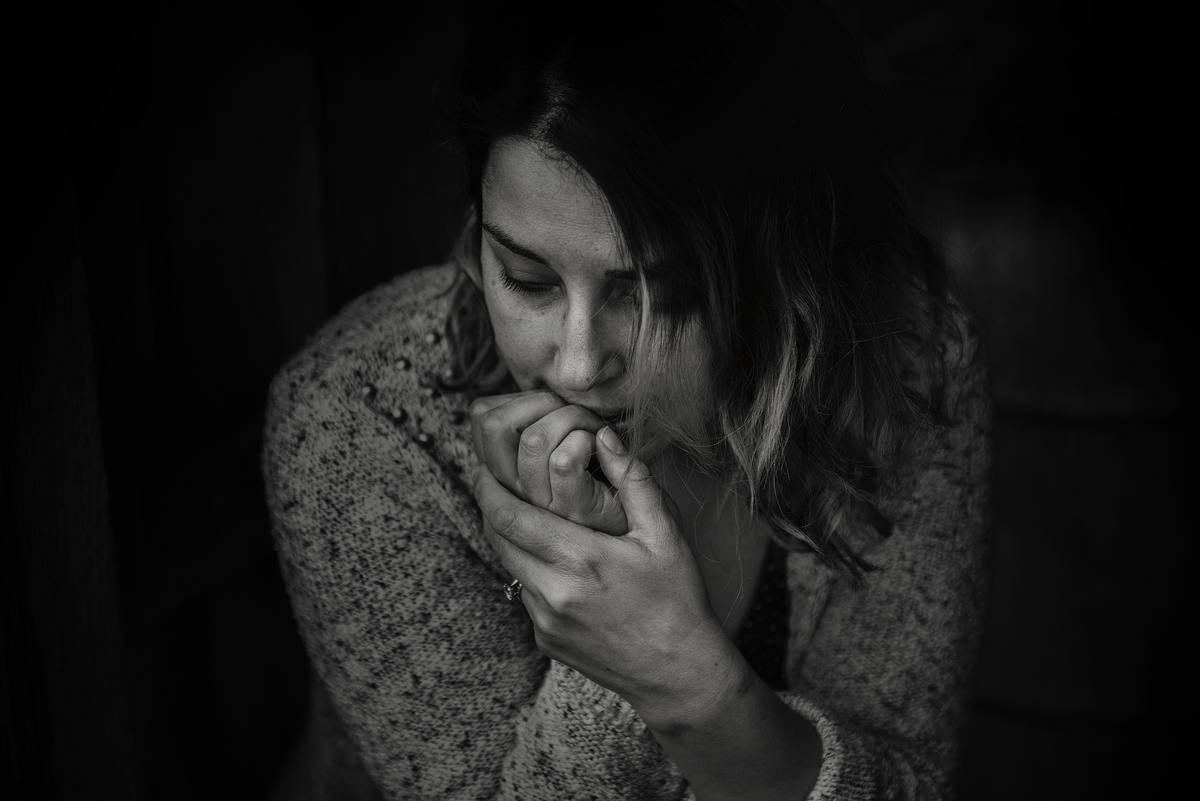 woman looking down and biting her nails