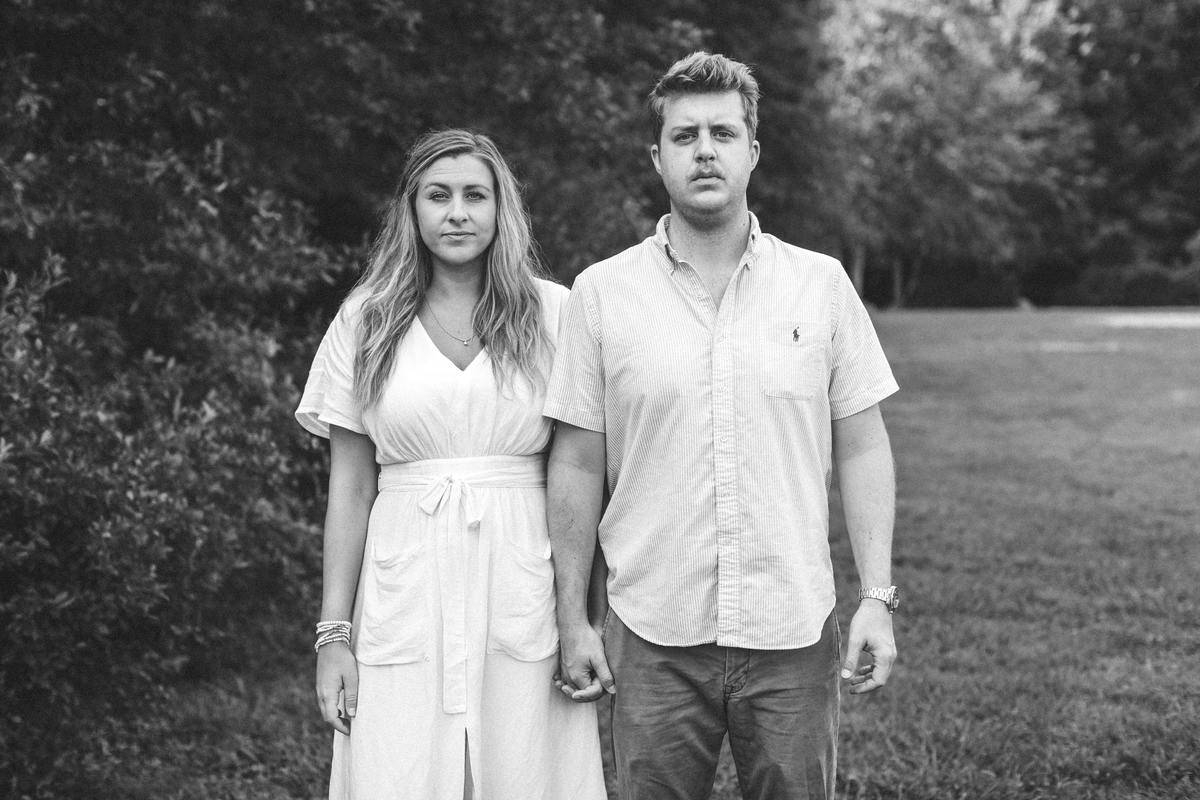 couple standing staring at camera holding hands black and white