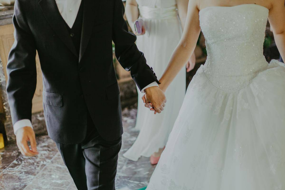 bride and groom hold hands and walk