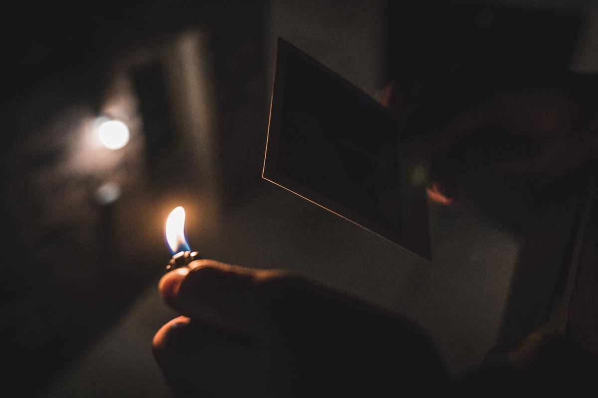 Person holding a lighter close to a photograph