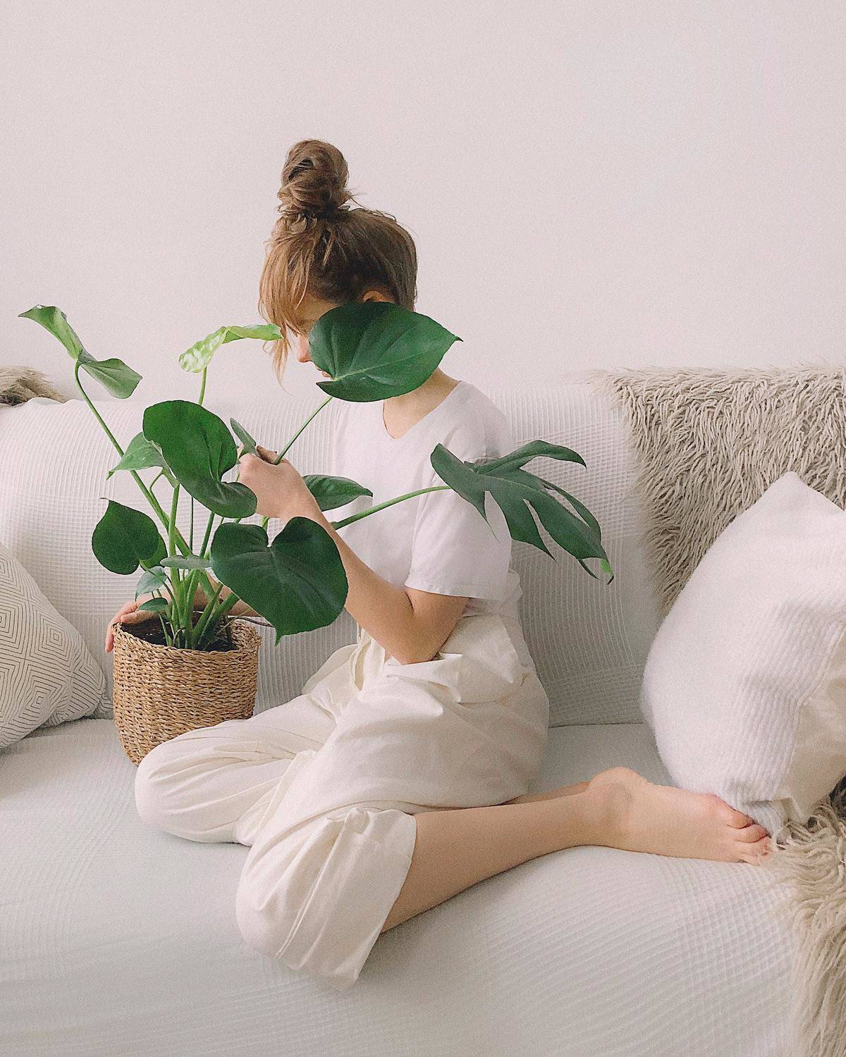 woman sitting on a couch looking at a plant