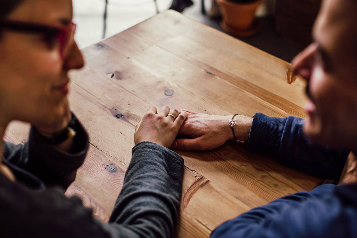 couple holding hands over wooden table