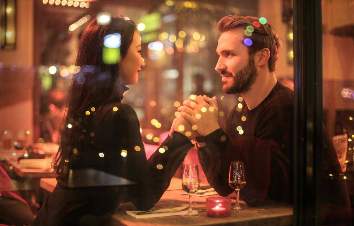 couple holds hands at restaurant date