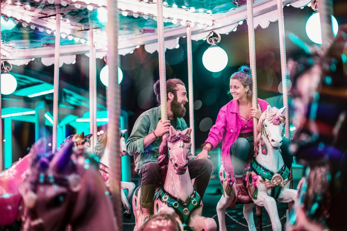 man and woman riding colorful carousel at night