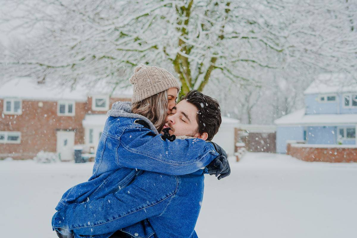 couple outdoors playing in snow in jean jackets
