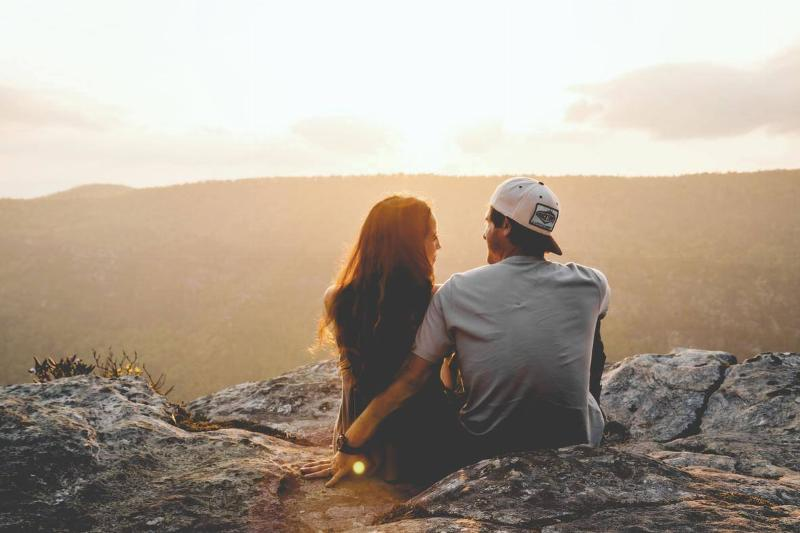 couple sitting on cliff and smiling at sunset