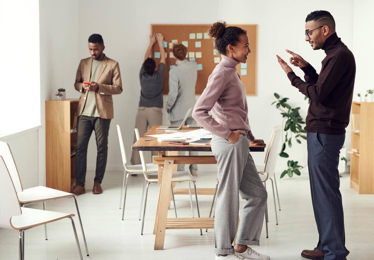 man and woman standing having discussion in office