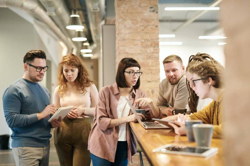 coworkers in workplace standing at coffee bar