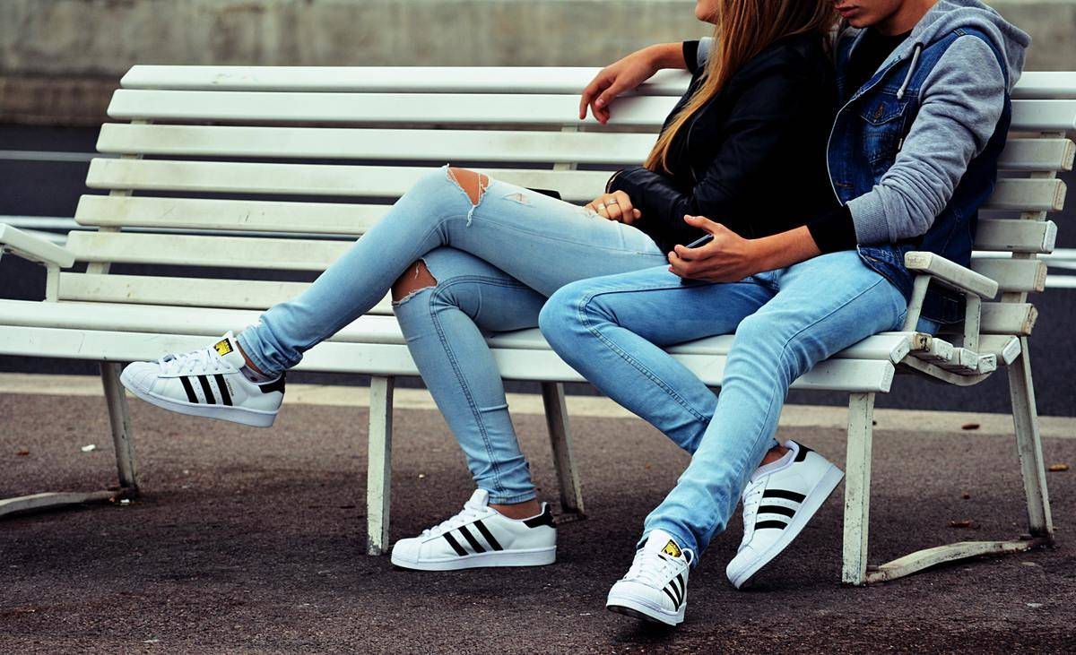 cropped out couple sitting on bench in jeans and matching sneakers