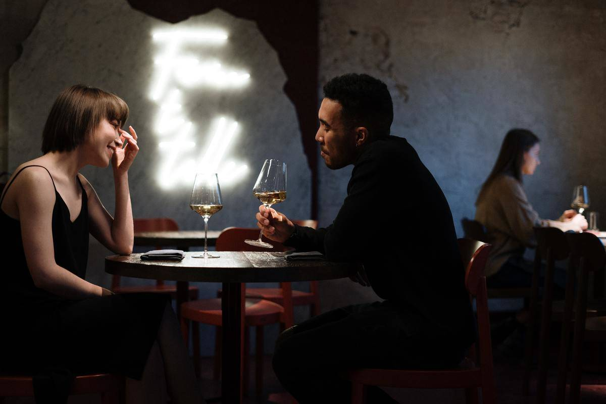 couple sitting in a restaurant with glasses of wine
