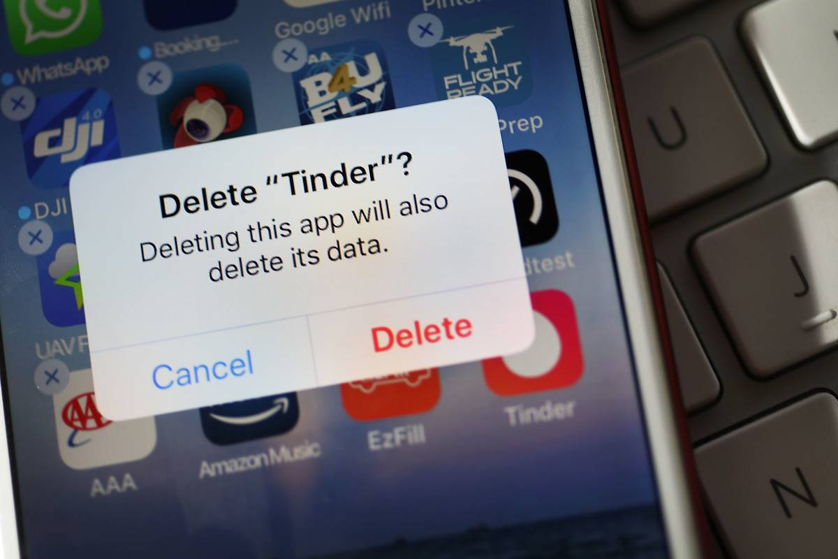 Person deleting Tinder app on phone screen
