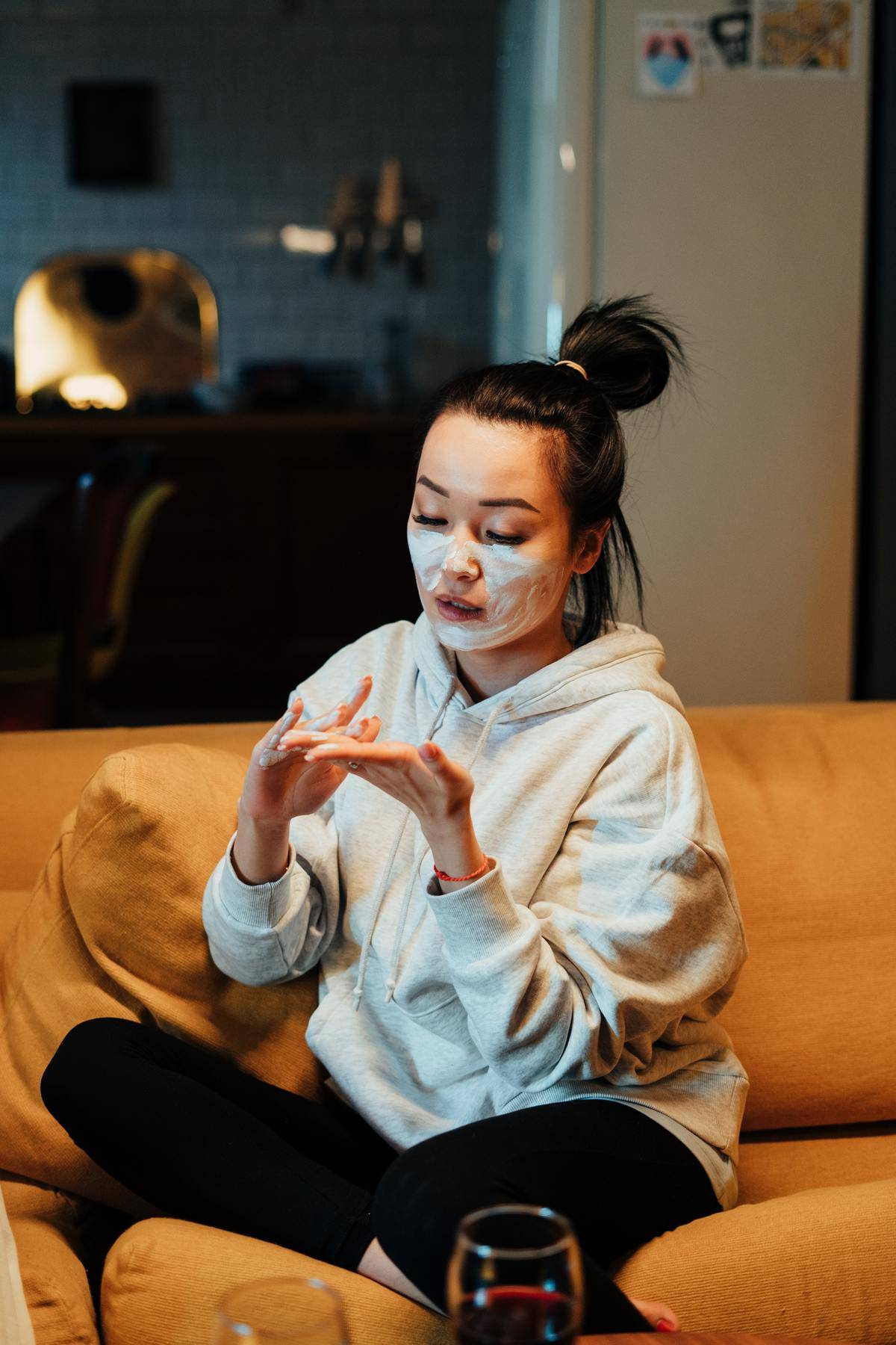 a woman putting on a face mask sitting on a couch with a glass of wine
