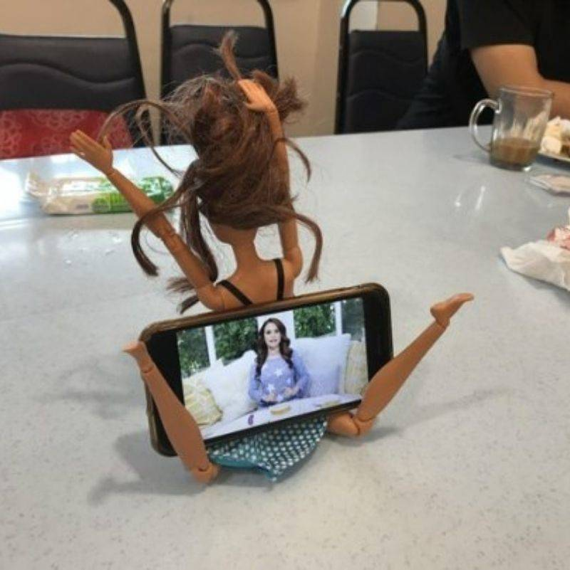 someone using a doll's legs to hold up their phone