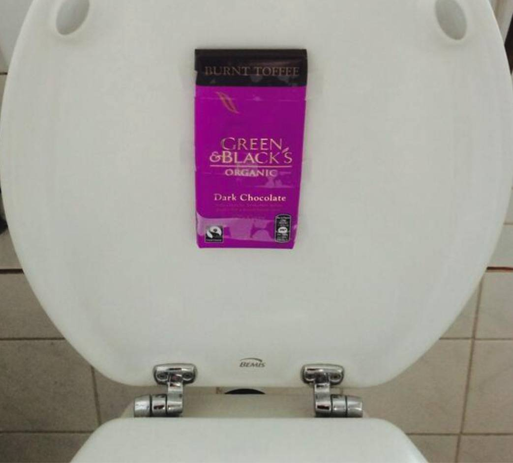a toilet seat with a chocolate bar taped to the underneath of it