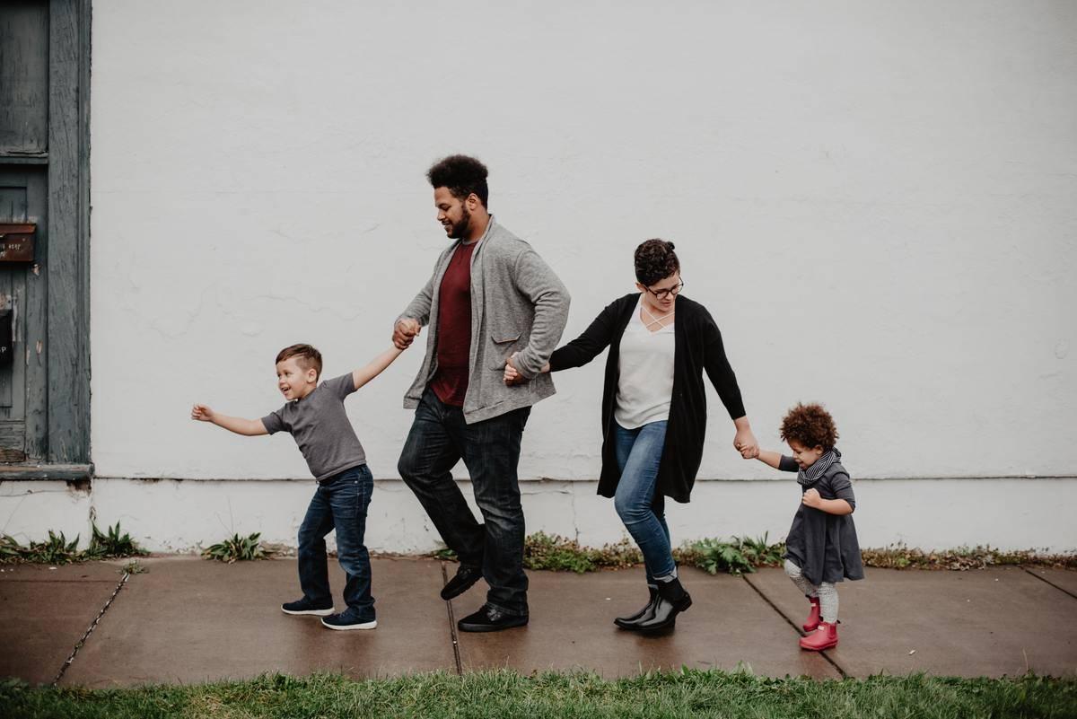 parents walking kids on sidewalk