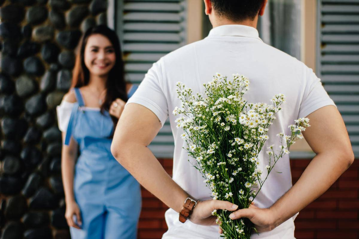 man walking up to  woman with flowers hidden behind his back