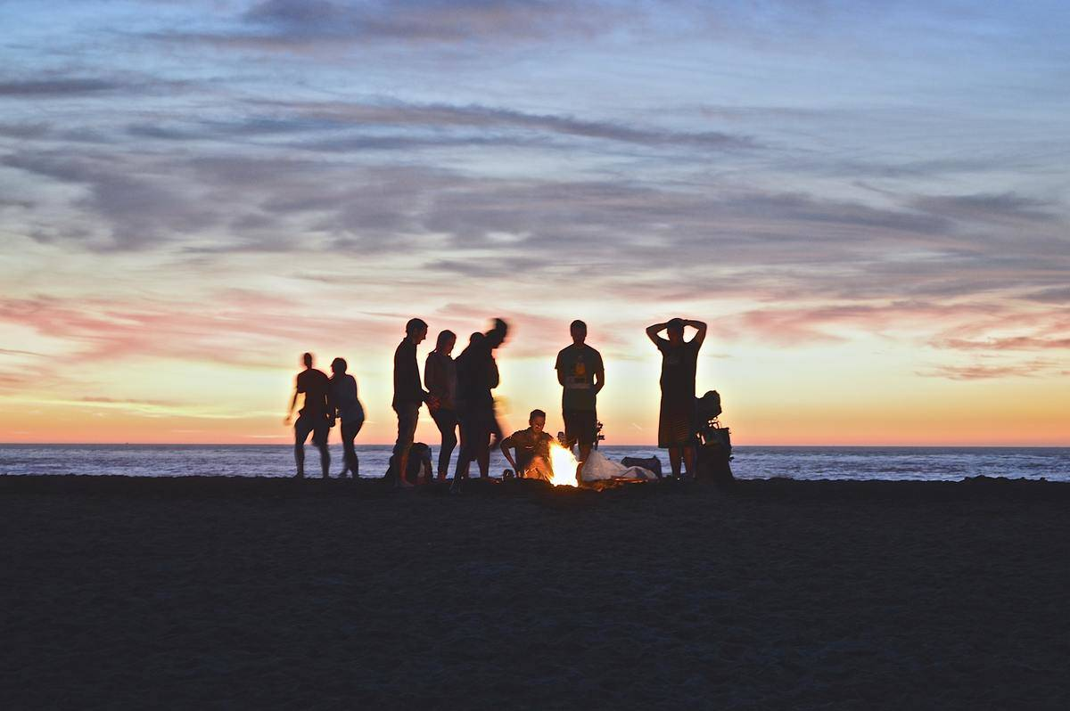 large group of friends at sunset by bonfire