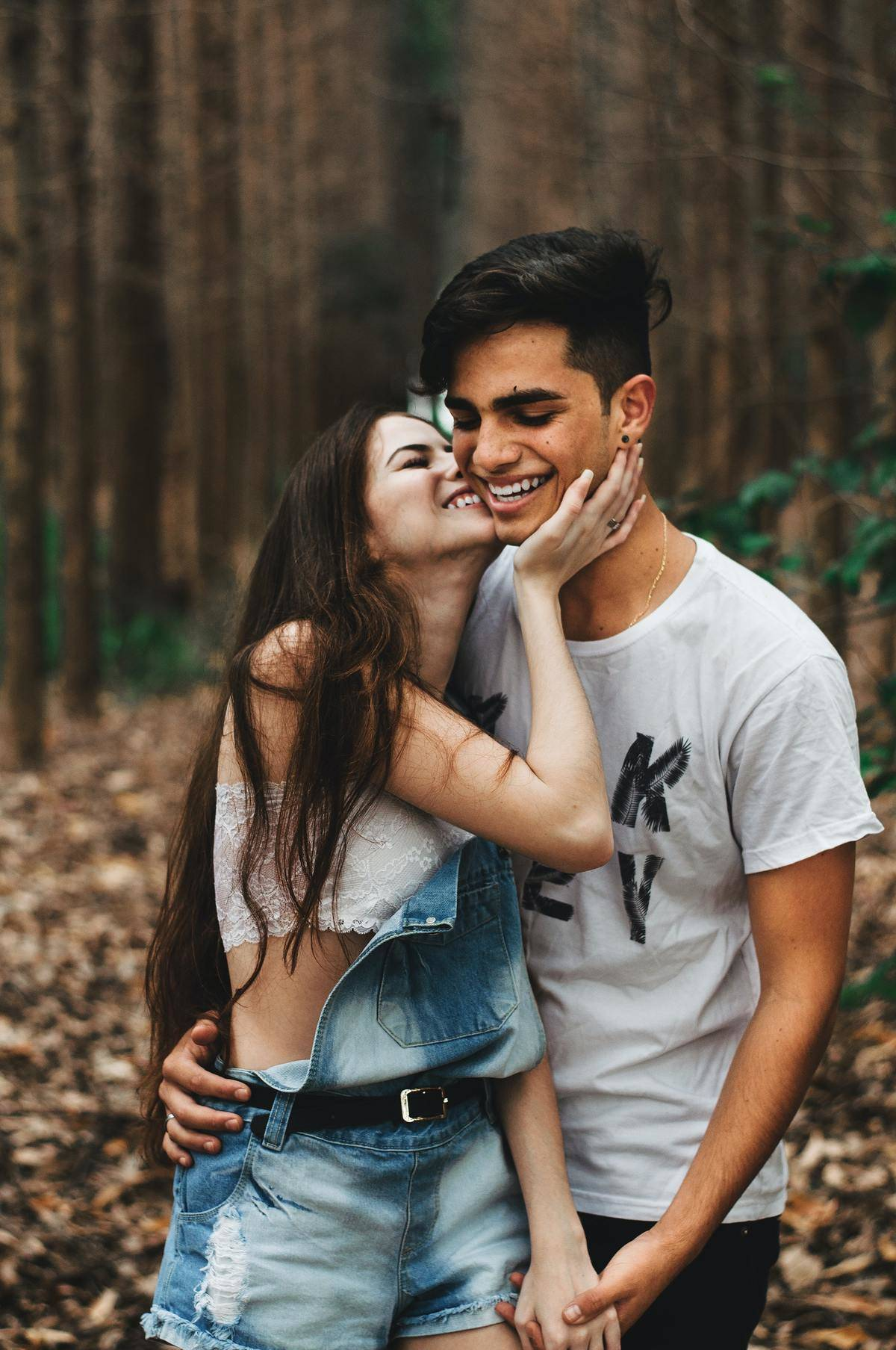 a couple walking on a trail laughing together while she gives him a kiss on the cheek