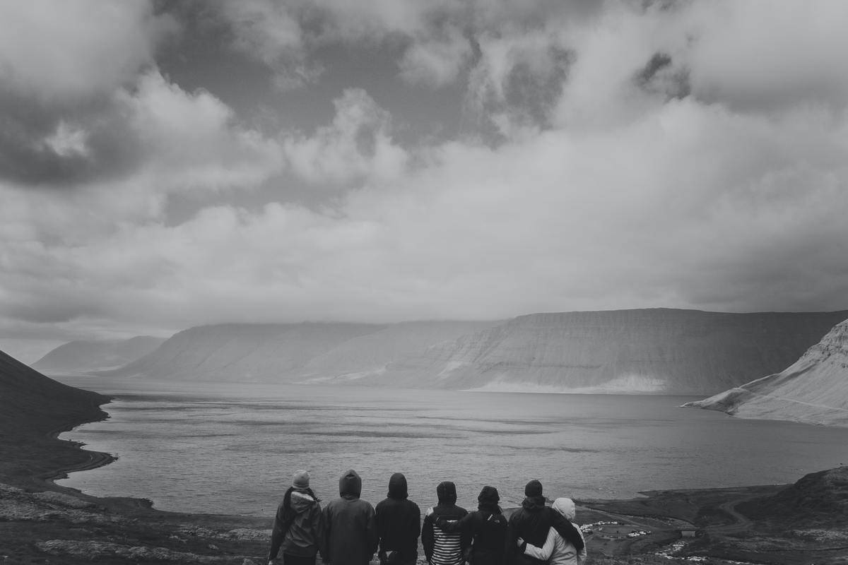 black and white photo group of friends staring out at landscape