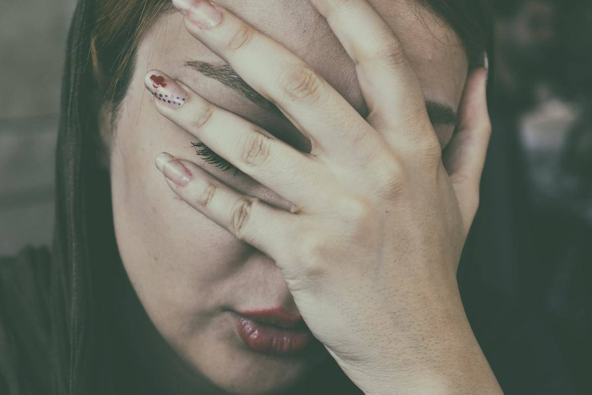 woman looking stressed with her hand on her face