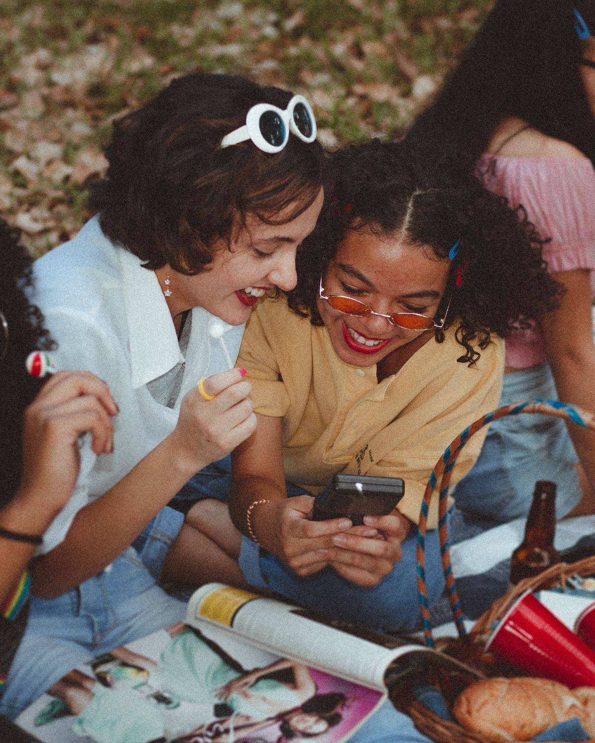 friends looking at a phone while having a picnic