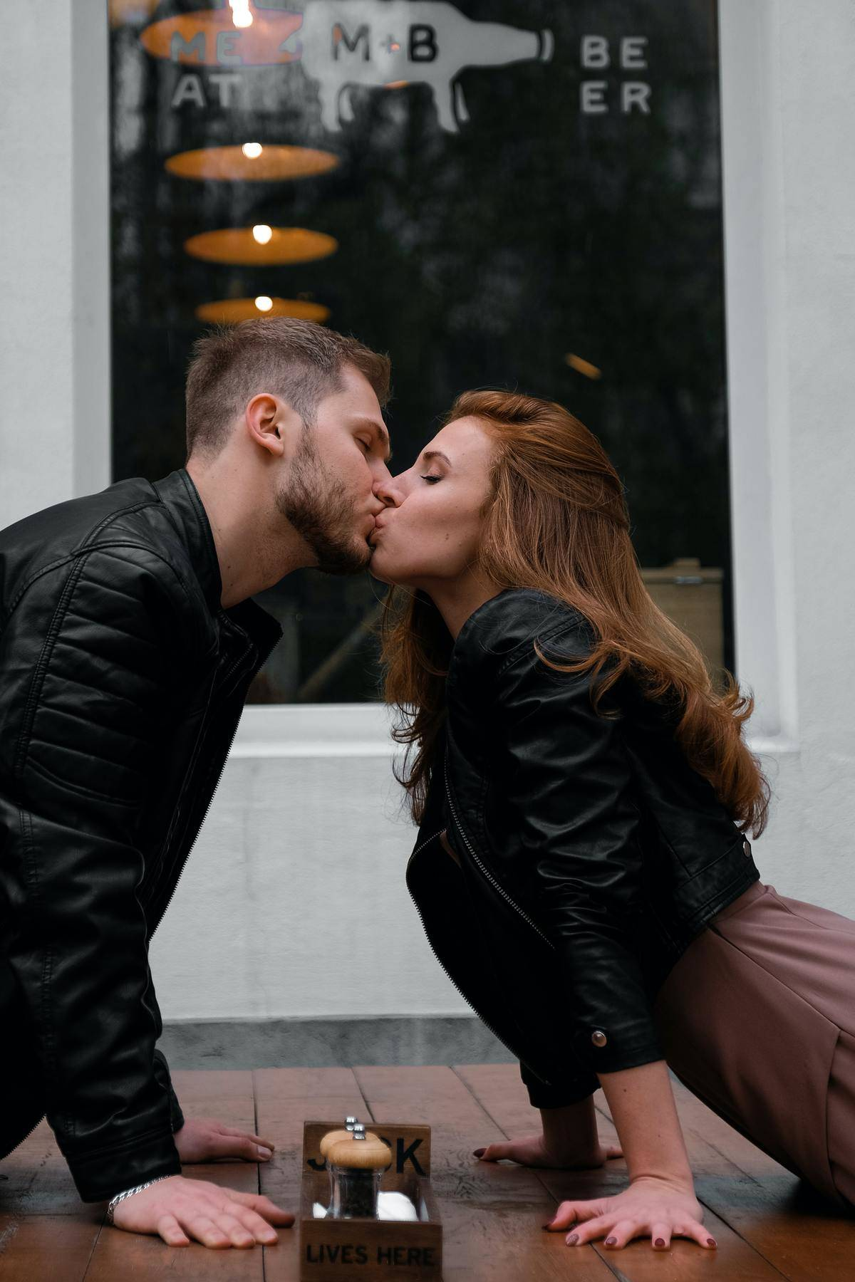 couple leaning over a table giving a kiss