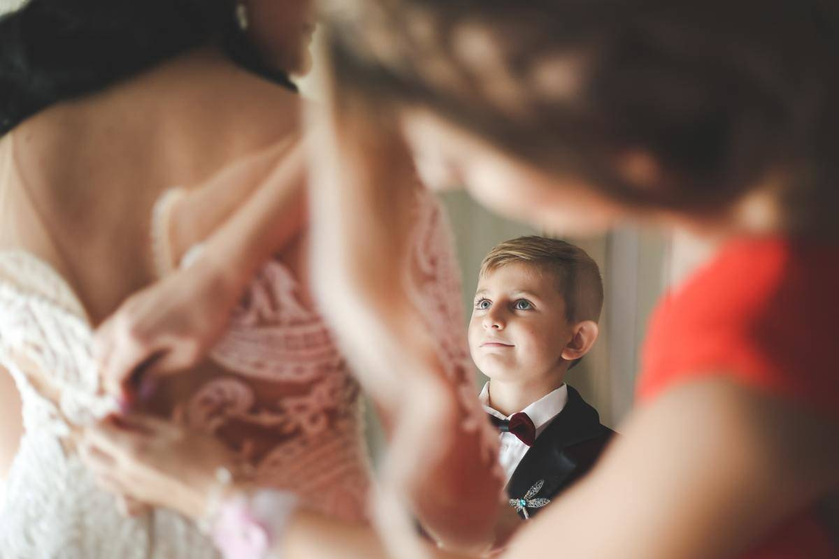 little boy looks up at bride