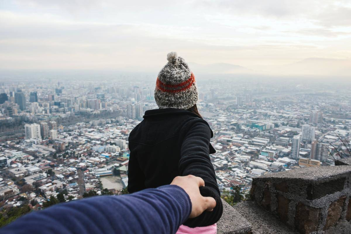 a girl standing in front of a guy holding is hand looking out at a city