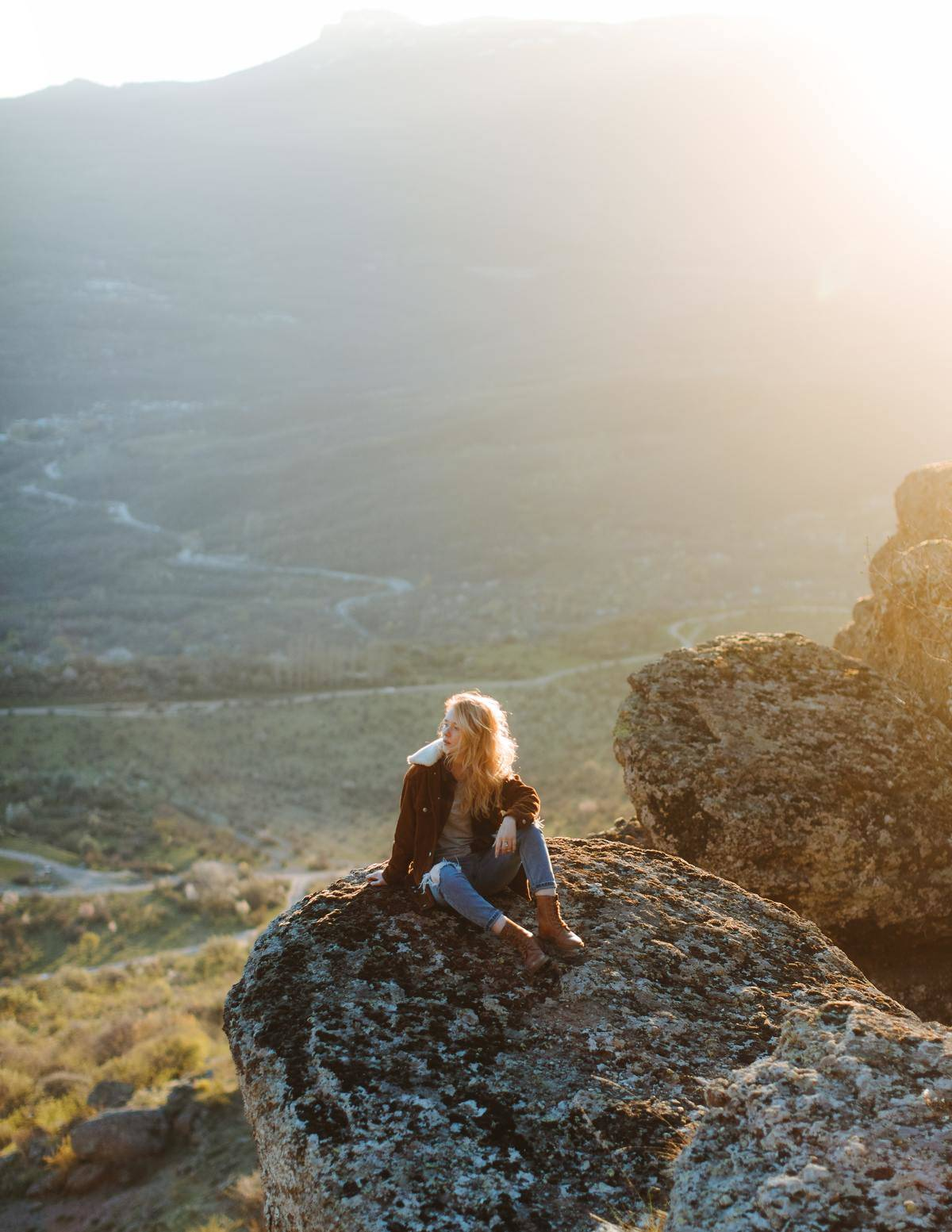 woman sitting on the side of a hill looking out over some nature scenery