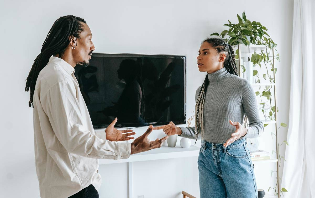 man and woman standing in living room arguing