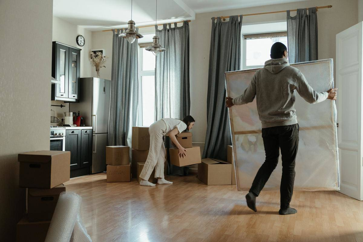 man moving large frame out of apartment woman lifting box