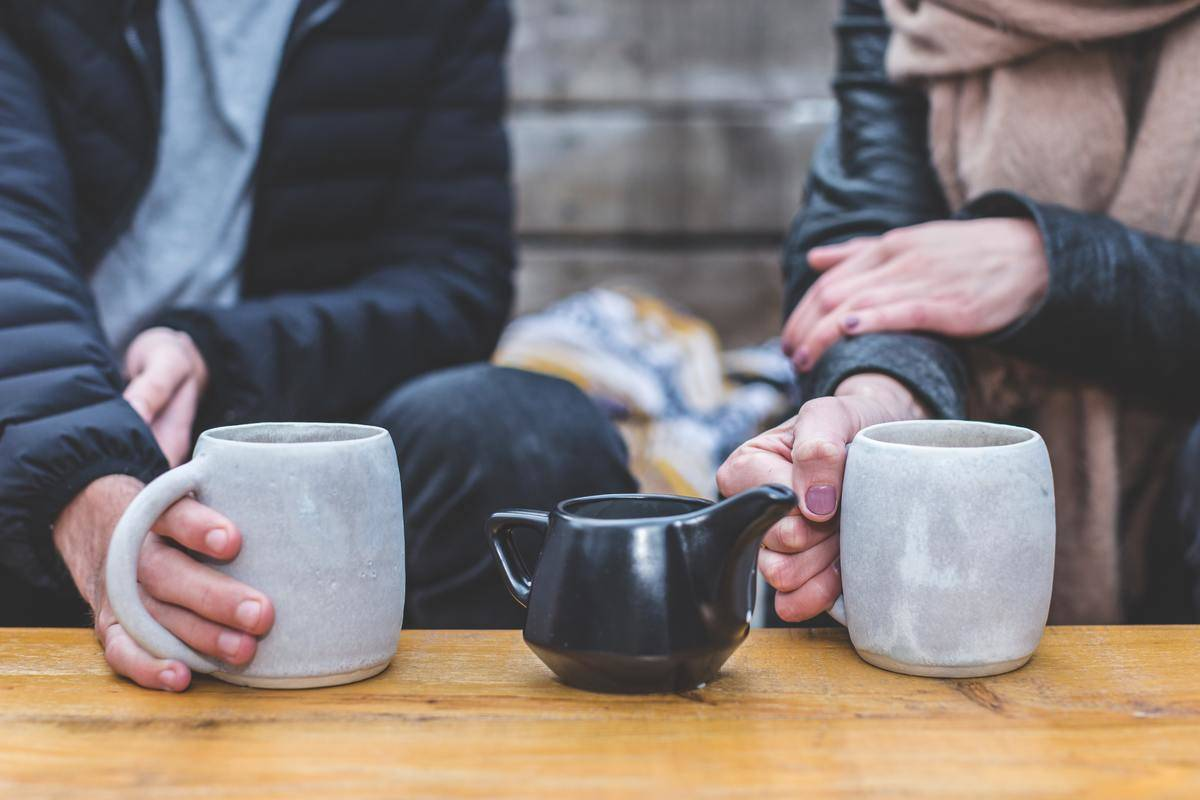 man and woman seated outdoors with coffee mugs and tea pot