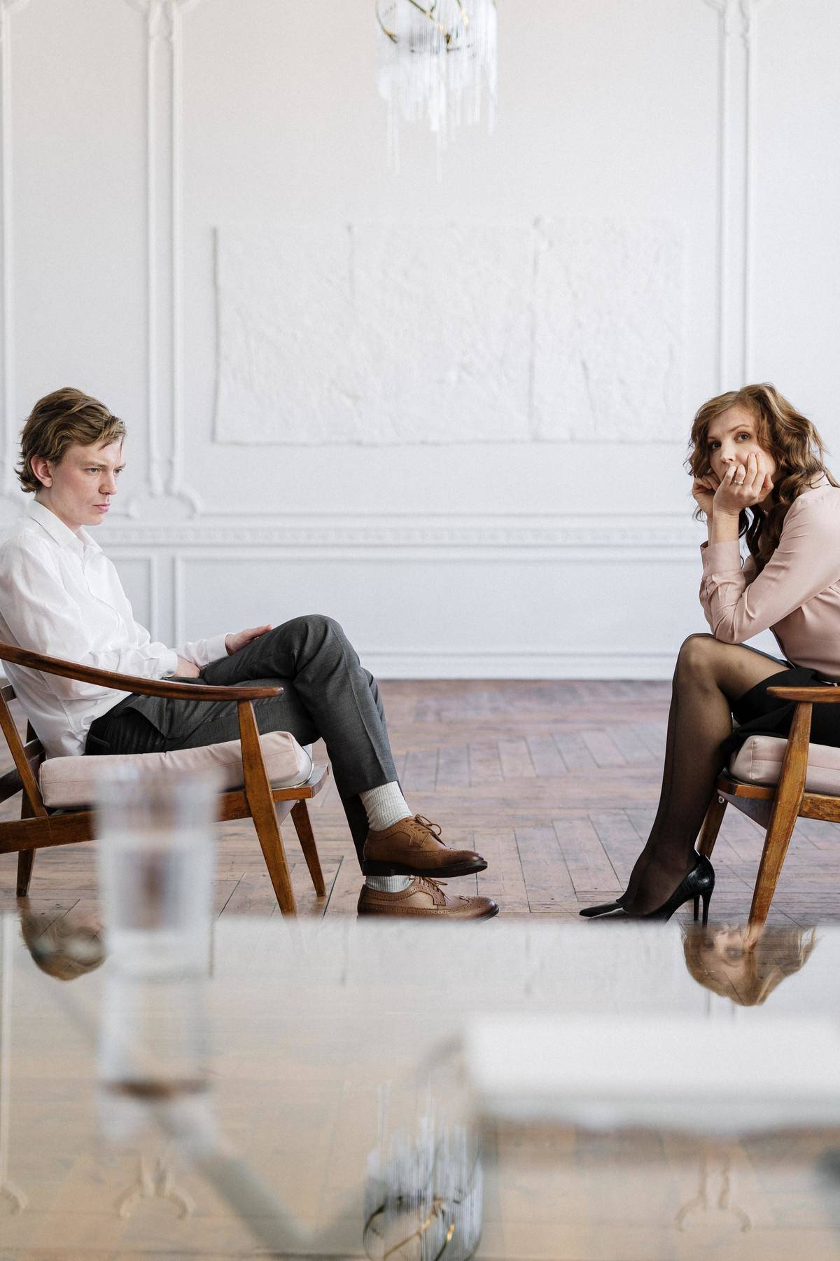 man and woman sit at therapists office across from each other