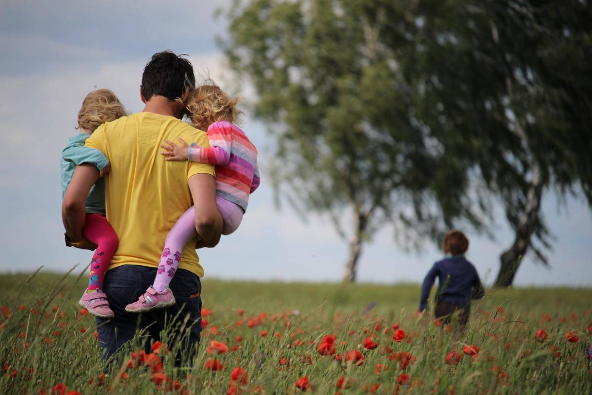 man carrying two kids in a field