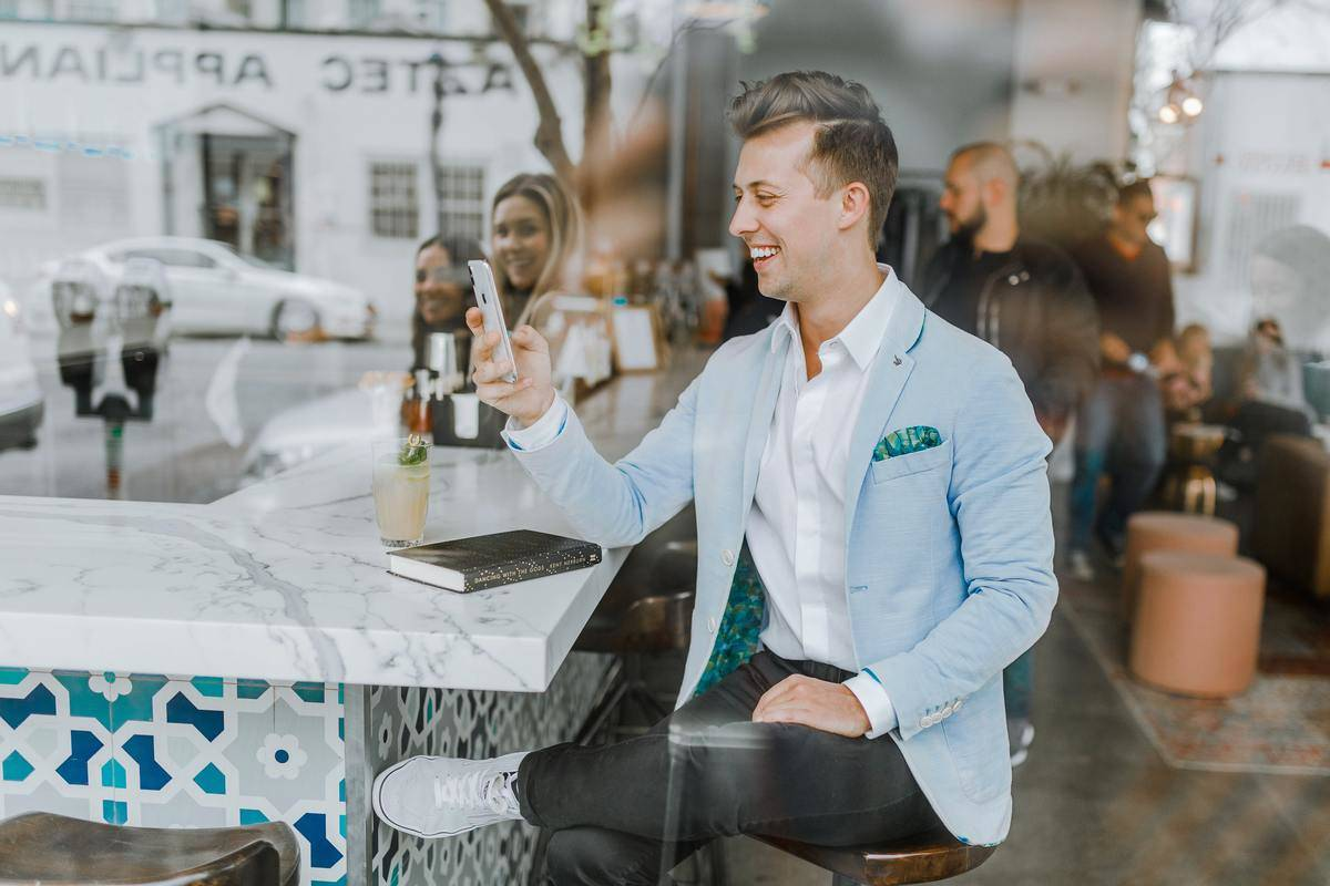 man in blue suit jacket seated at restaurant bar laughing at phone