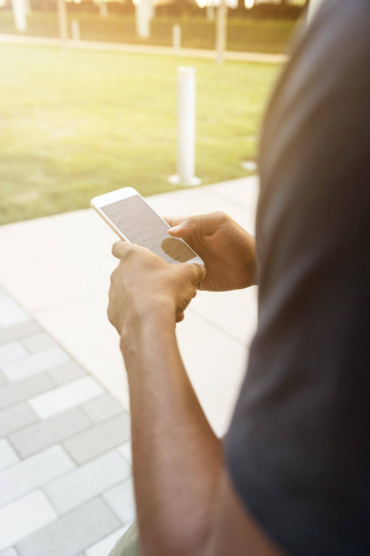 man holding phone standing outside