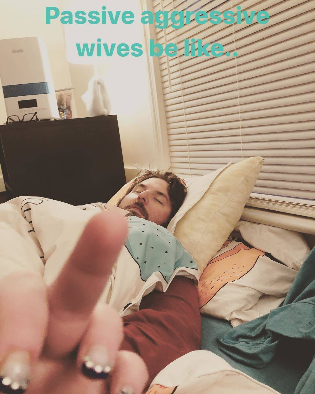 woman giving her husband the middle finger while he sleeps