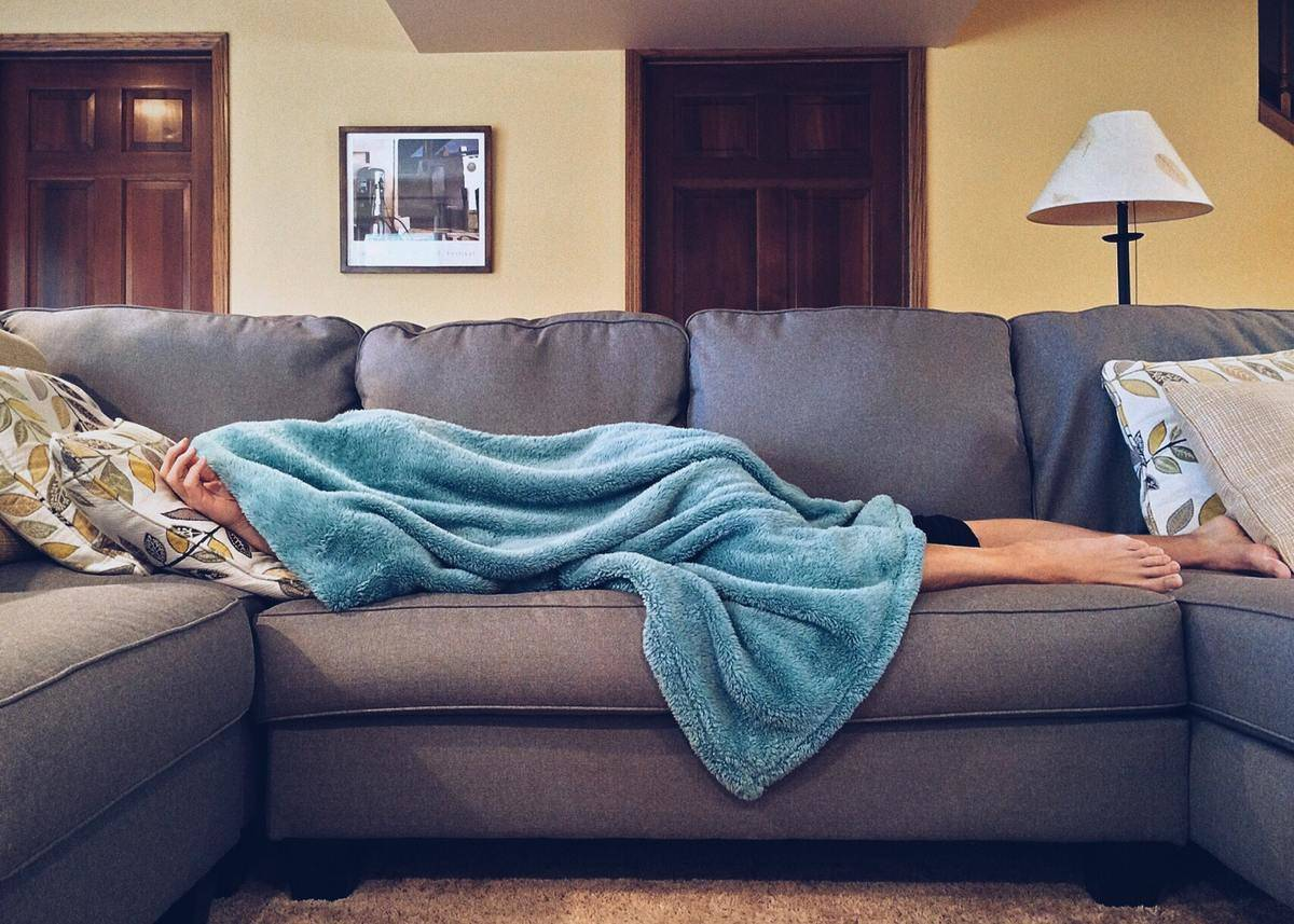 someone lying on the couch with a blanket covering them