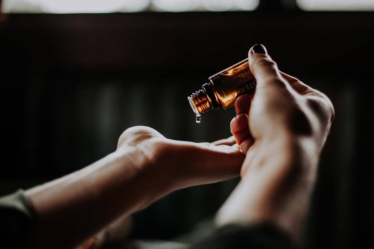 person pouring massage oils onto hand