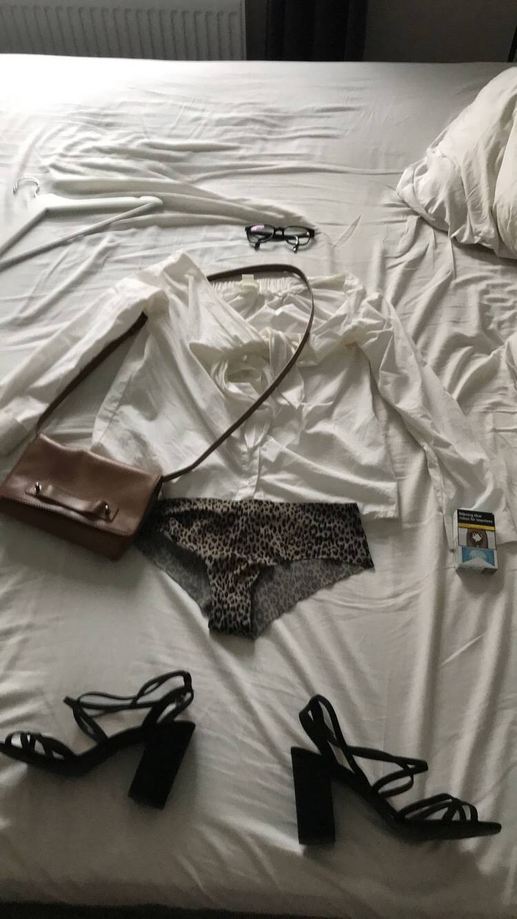 a shirt, purse, underwear, and shoes laid out on a bed