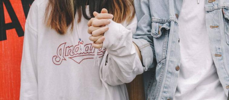 couple holding hands woman in long sleeve man in denim
