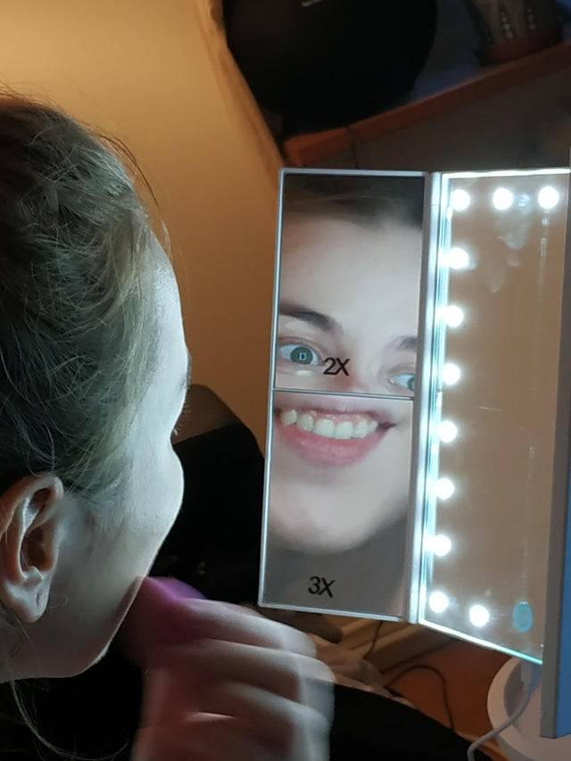 boyfriend took picture of girlfriend looking in makeup mirror with two different magnifications