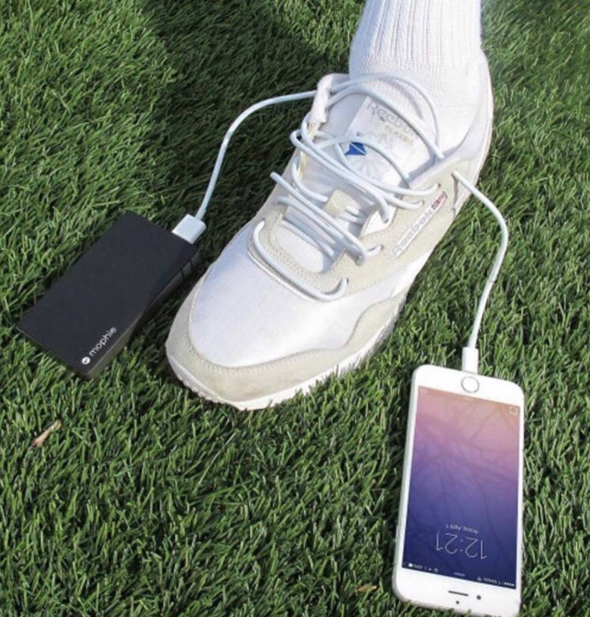 someone with a phone cord as a shoelace. One side is plugged into a phone and the other is plugged into a portable charger