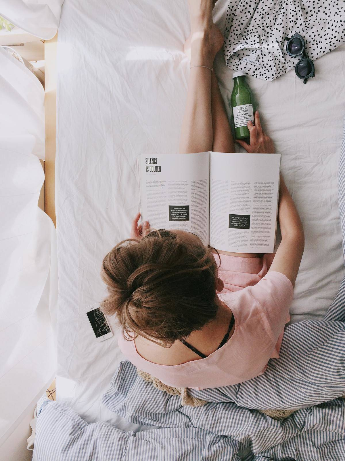 woman reading a magazine in bed with a juice sitting next to her and her phone