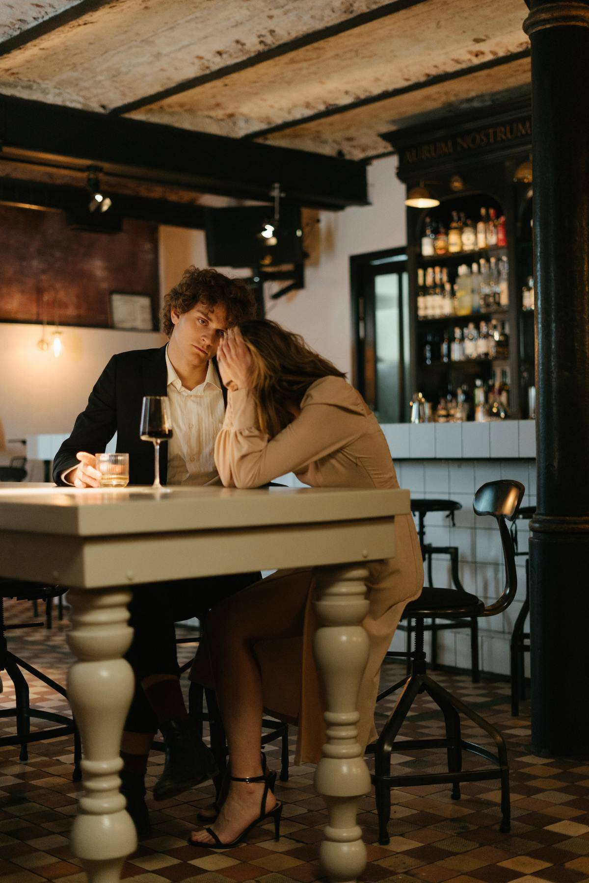 man looking at woman with head in hands at restaurant