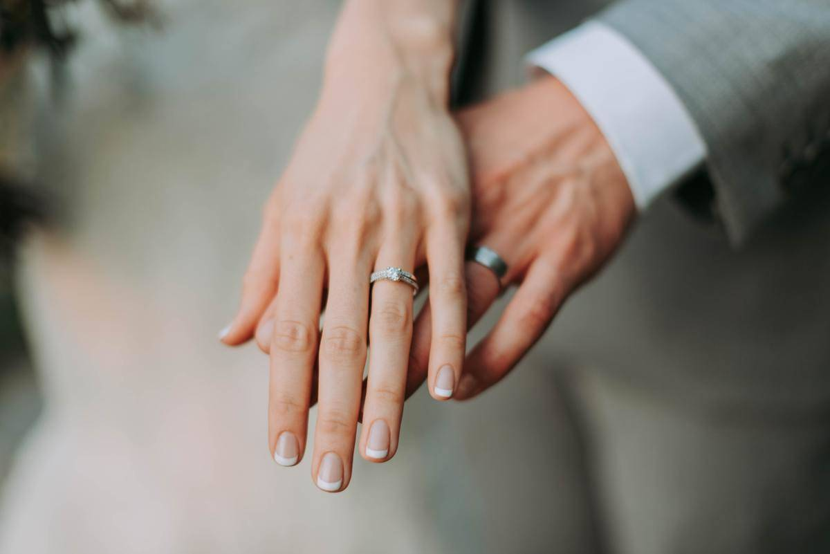 man and woman showing off wedding rings