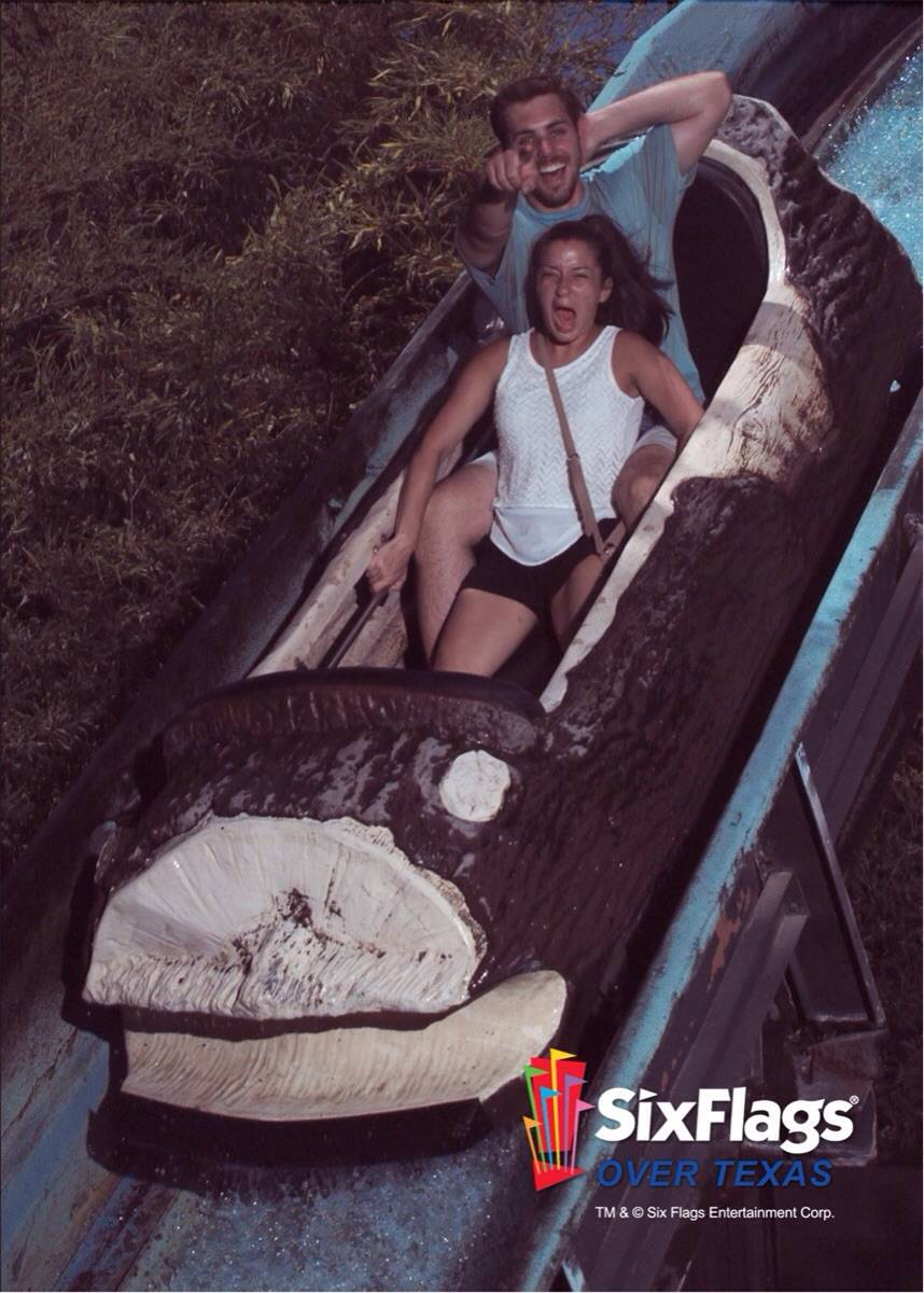 two people on a roller coaster and one of them is pointing at the camera and the other is terrified
